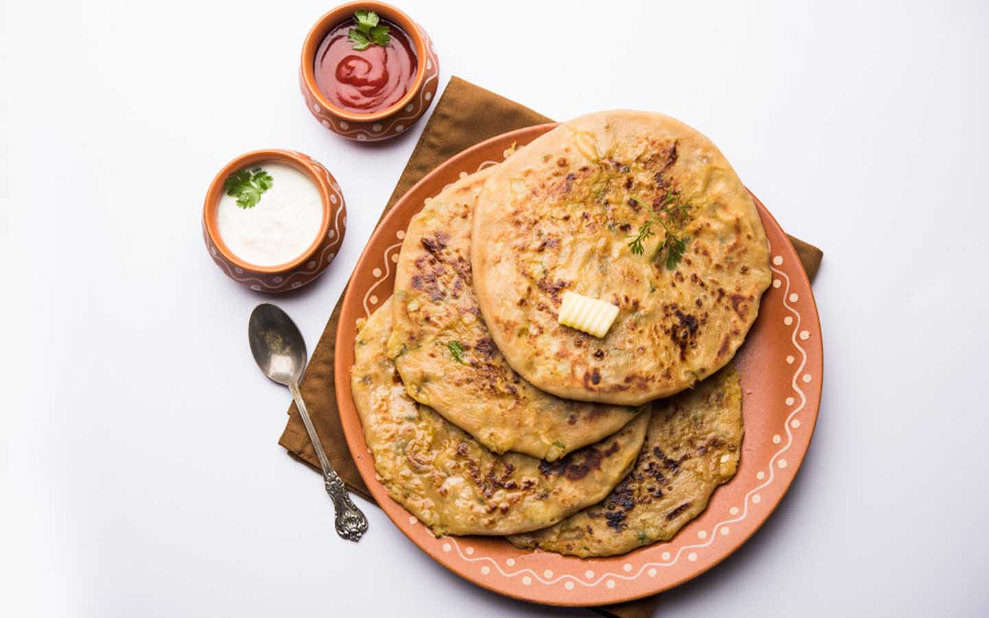 Cauliflower paratha served with dips and cheese