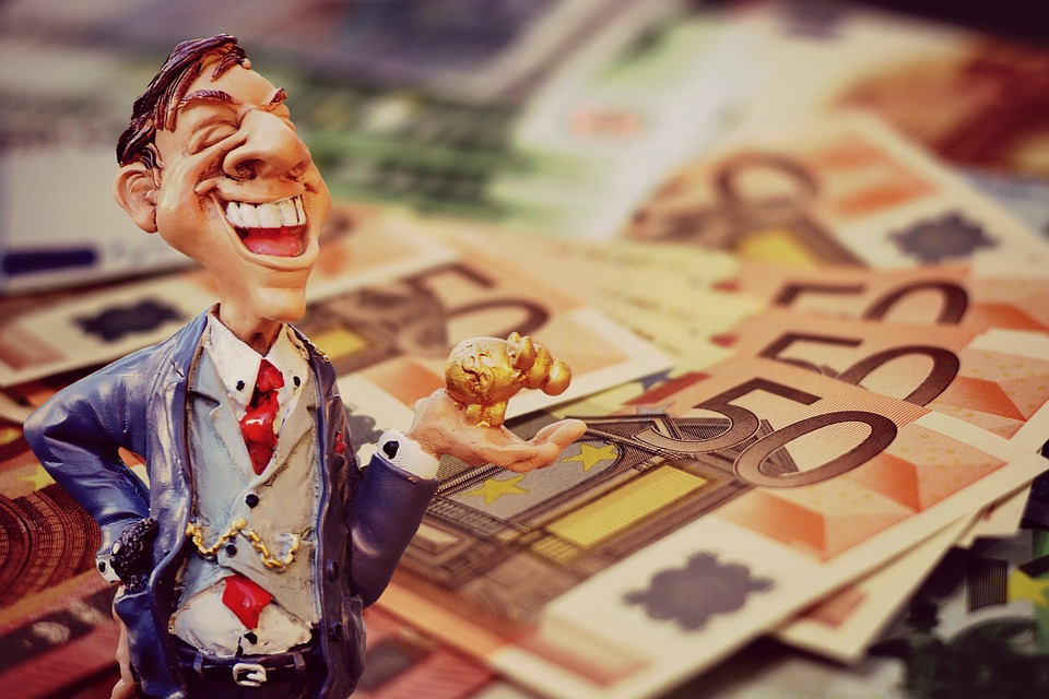 A figurine of a smiling businessman holding a piggy bang next while standing on a stack of euros