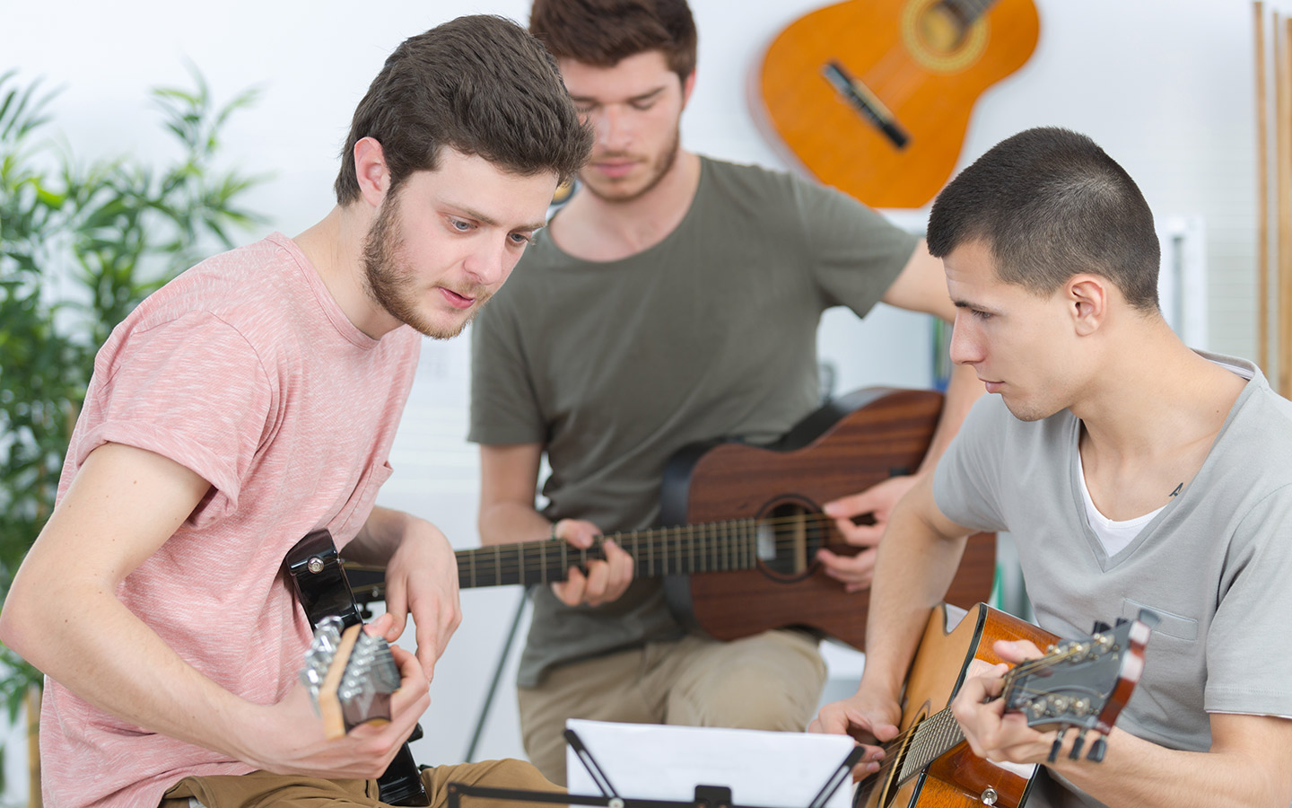 Students are learning to play guitar in a music school