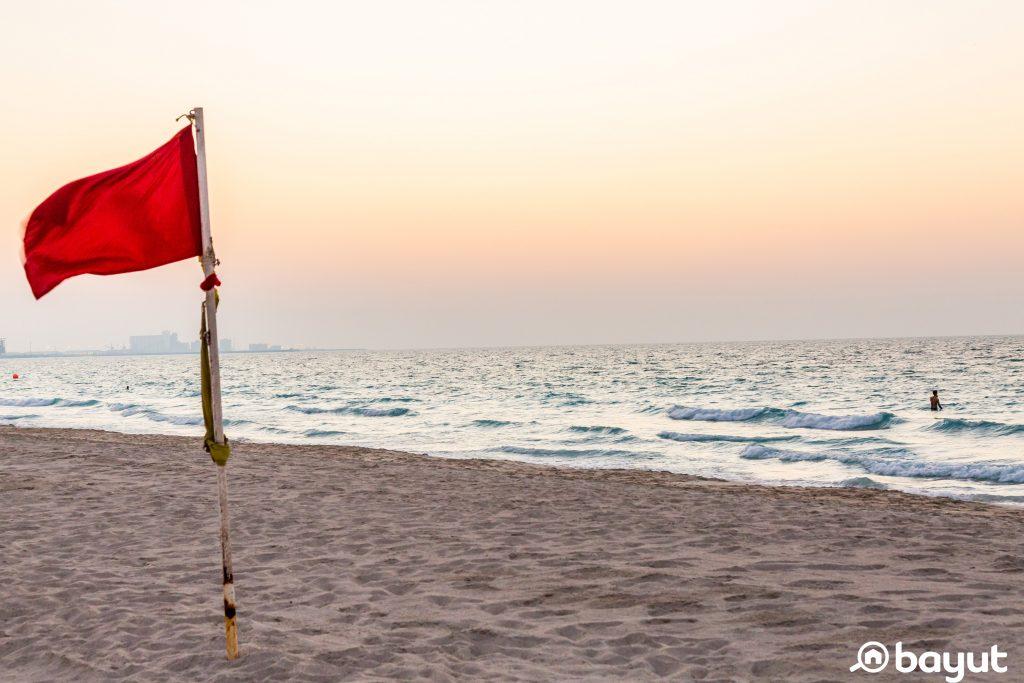 A red flag on Saadiyat Beach in Abu Dhabi at sunset