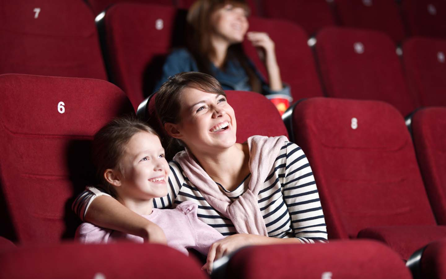 Girl is watching a movie with her mother