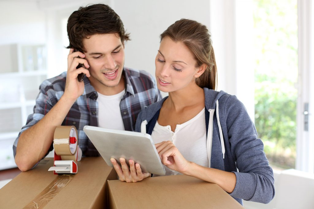 A young attractive couple stands next to a pair of packed moving boxes, calling a moving company from the phone book