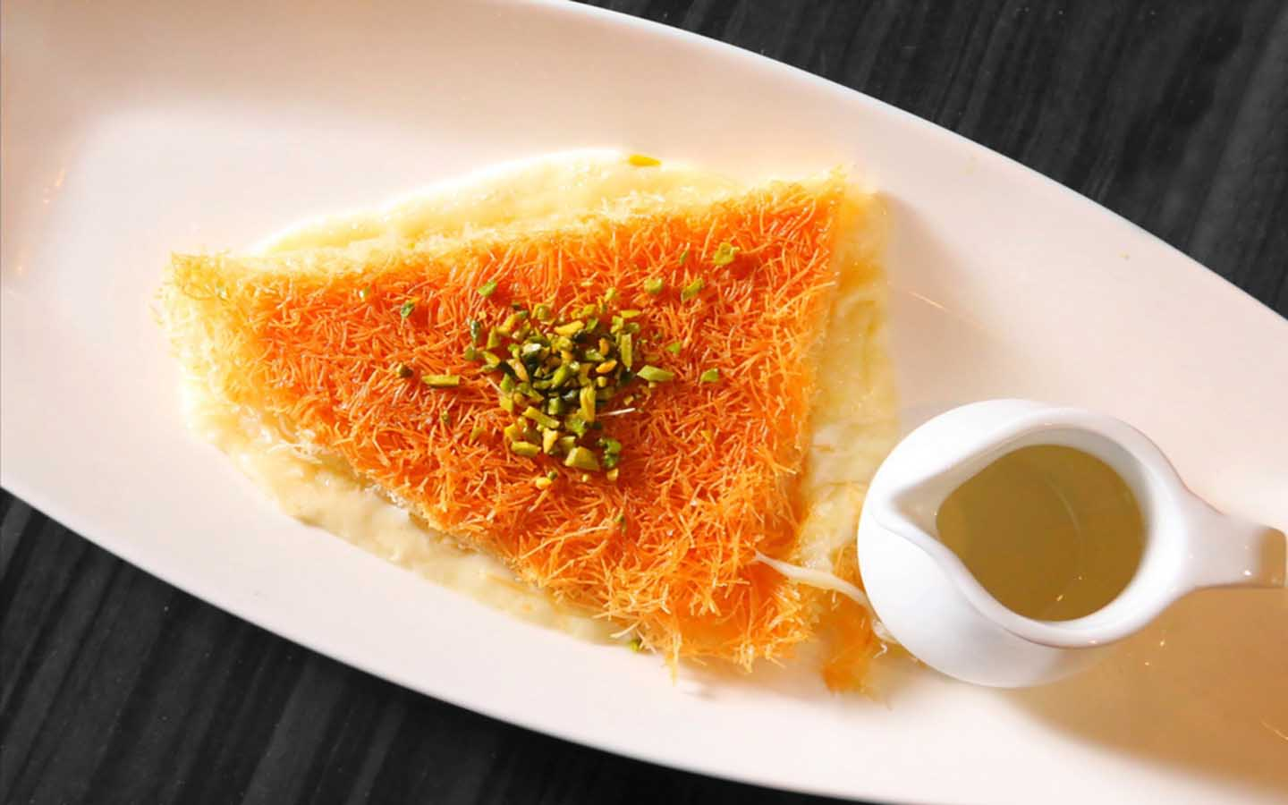 Kunafa on a plate with extra sweet syrup
