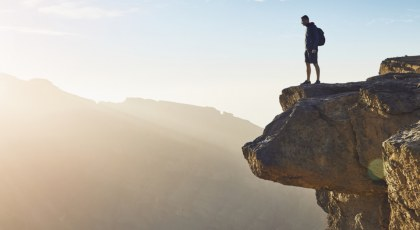 Man standing on top of a mountain ledge