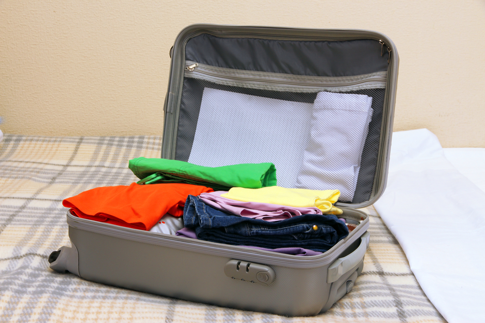 An open suitcase with a few clothes items for a short, one-day trip