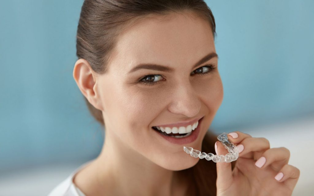 a lady showing her teeth aligners