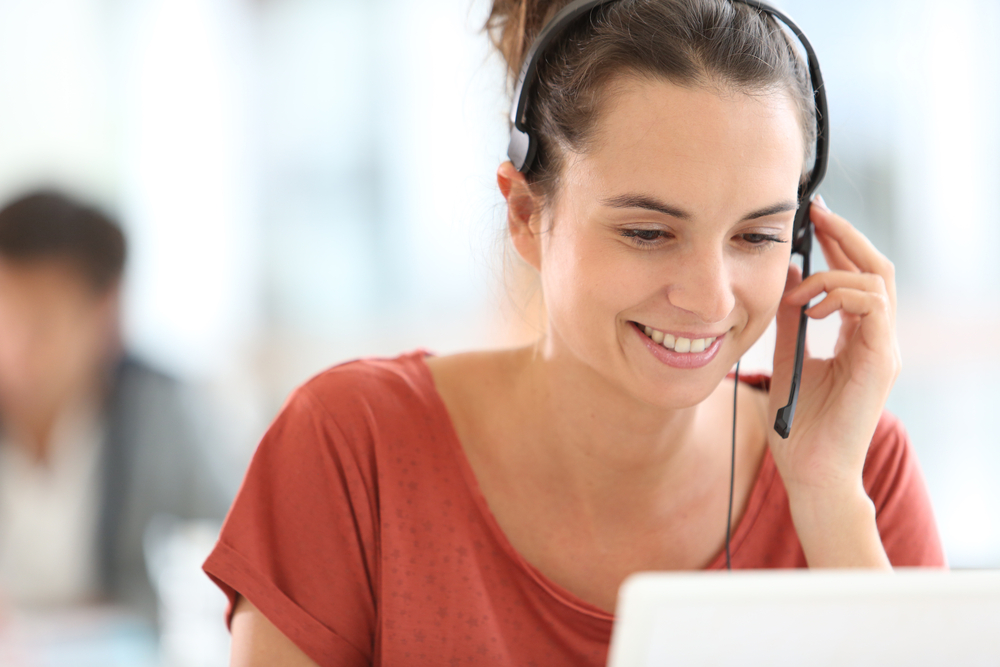 A young and beautiful female Call Centre worker sitting by her laptop talks on the phone using a headset with a smile on her face