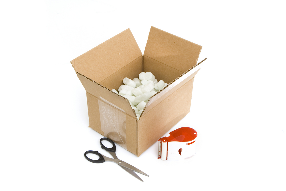 A small carton box open, with Styrofoam inside and scissors and tape next to it with a white background