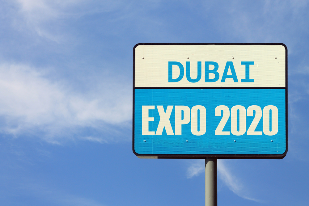A two-part road sign against a blue sky with 'Dubai' written on the upper part and Expo 2020 written on the bottom part