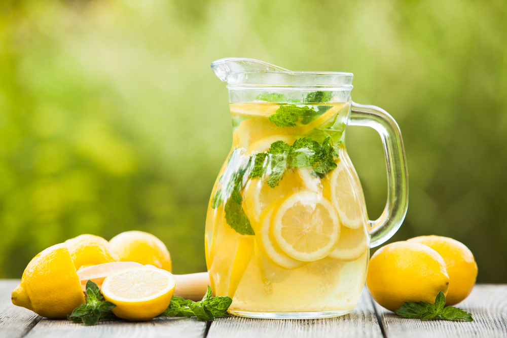 A jug of fresh lemonade with mint and extra lemon on the side on a table outdoor