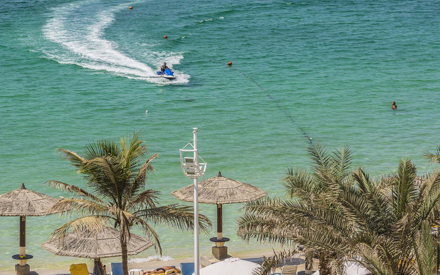 a person jet-skiing across Al Khan Beach