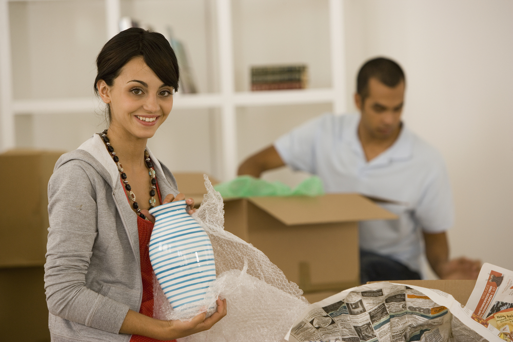 A young woman is wrapping a vase in bubble wrap, while her husband packs another box in the background