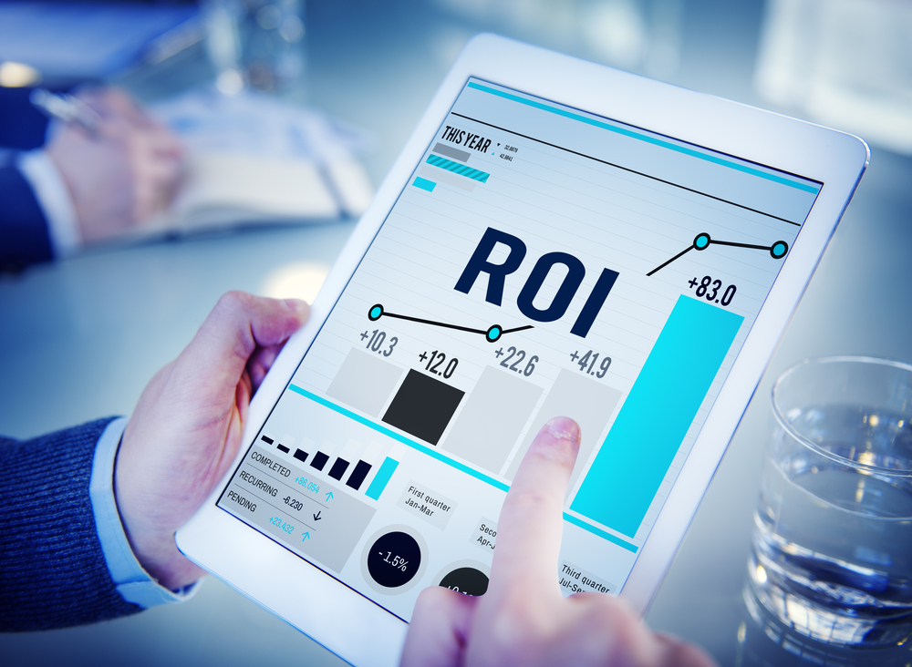 A businessman's hands operating a white tablet with graphs showing a rise in ROI (return on investment)