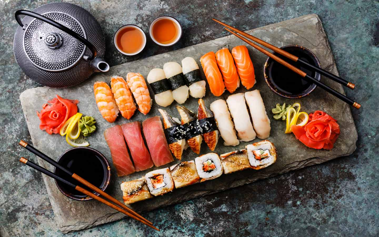 Assorted shushi and sashimi on a tray with chopsticks