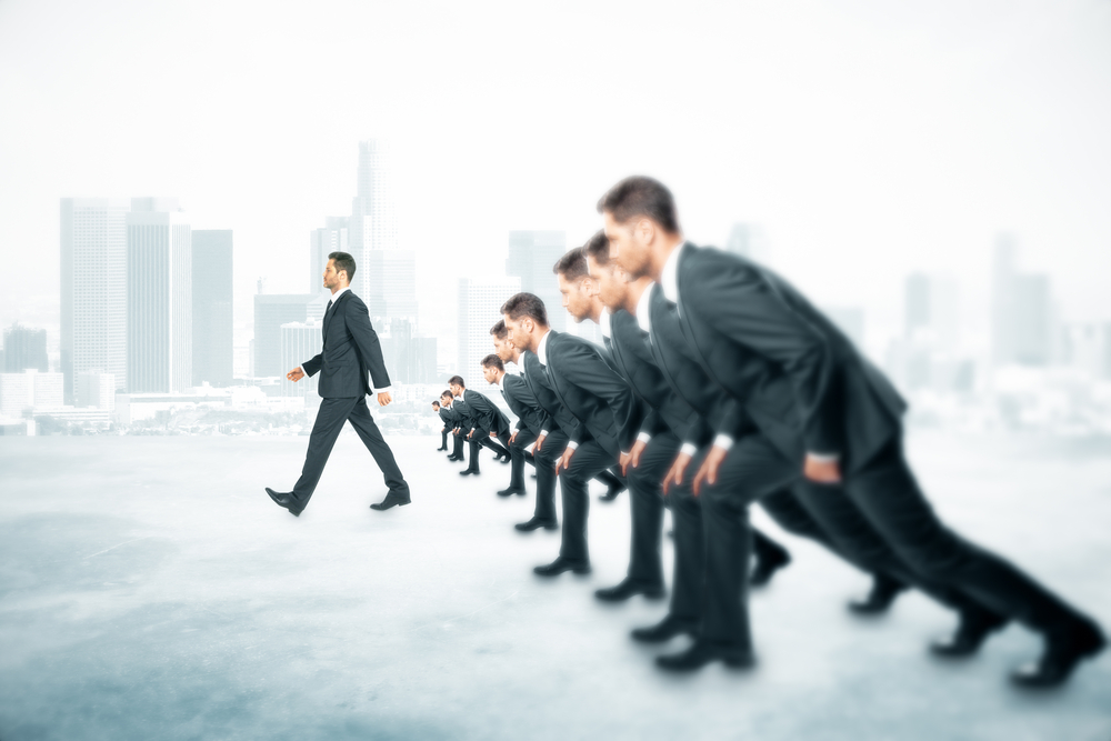 A group of businessmen in suits lined up in a sprint position with one of them walking away in clear advantage