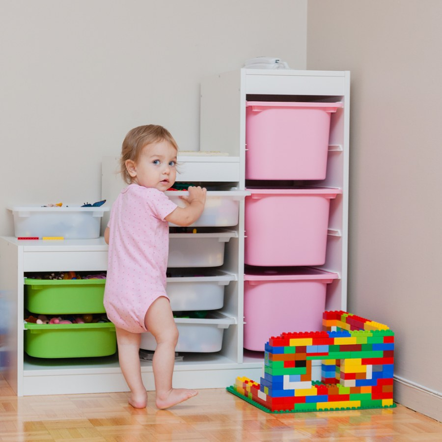A toddler is standing up to reach a toy from one of the many plastic containers in a tall space-efficient shelf