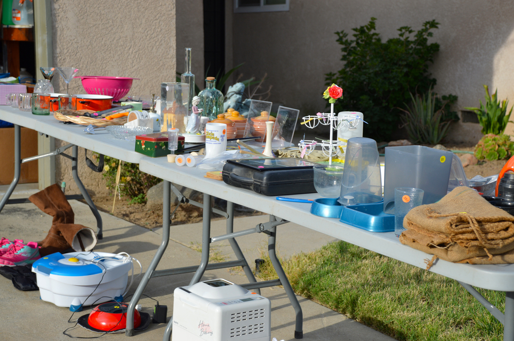 A yard sale with two two long tables and many unwanted kitchen and other items displayed for sale