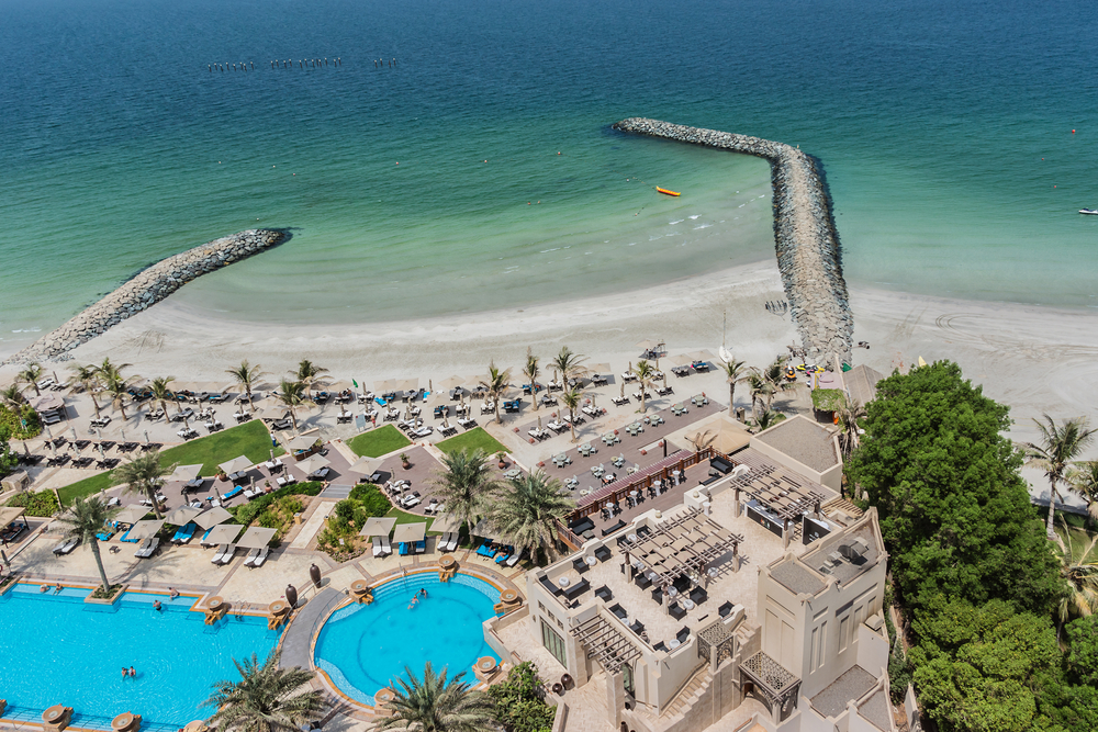 Birds-eye view of the Ajman Saray hotel in Ajman with the building on the right, two pools on the left and the crystal-clear water of the Arabian Gulf in the background