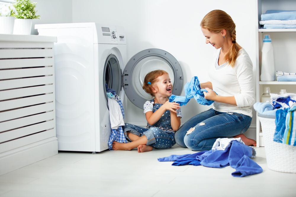 A child helps her mother load the washing machine to the fullest to save money