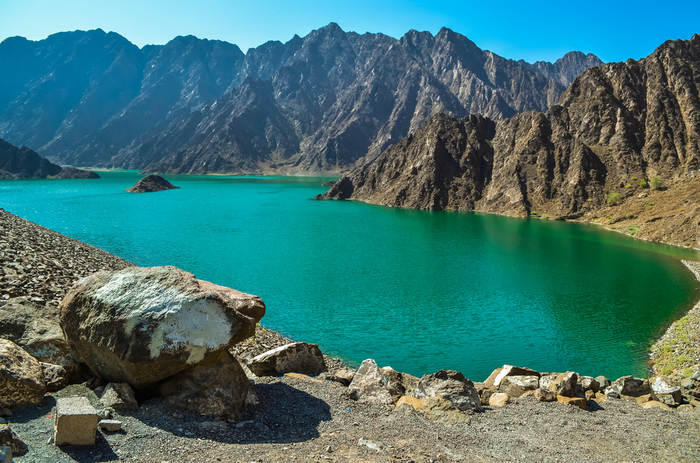 The Hatta Dam Green Lake with emerald-coloured waters and the Hatta Mountains surrounding it