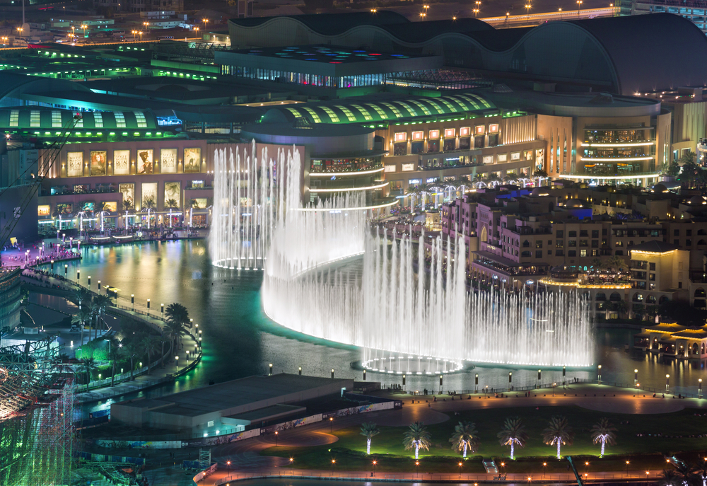 Dubai Mall lit up at night with the world's largest fountain ejecting water to its full extent