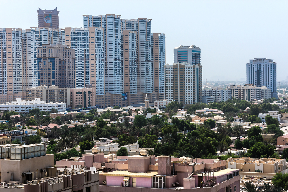 The cityscape of Ajman with tall residential buildings at the top and houses among trees at the bottom