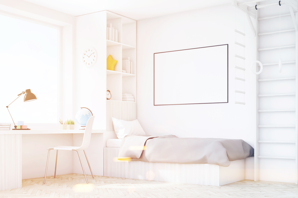 A bright child's room with white walls and an all-white bed, a writing desk and other bright-coloured furniture