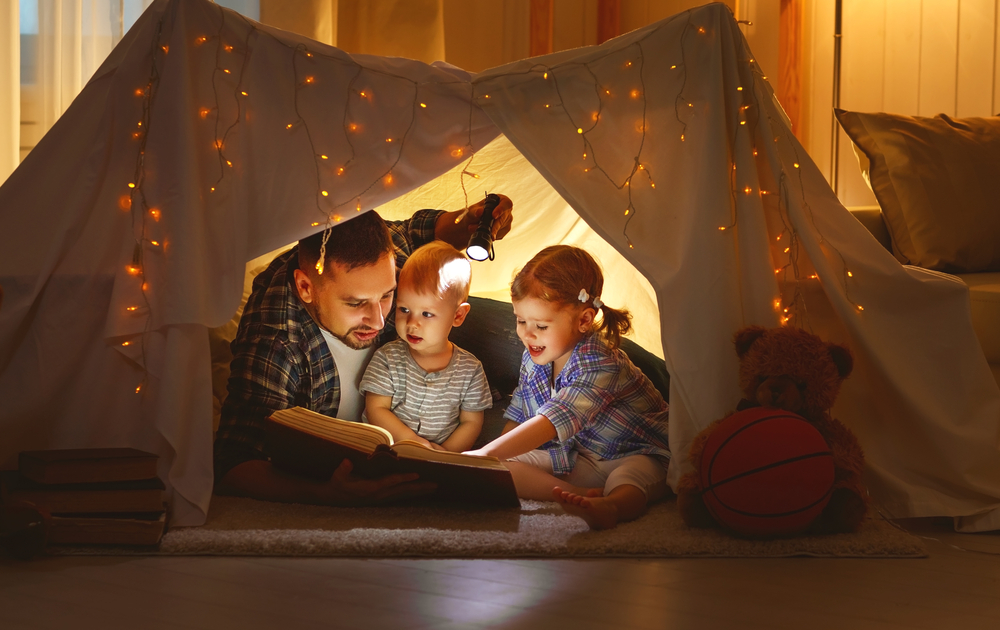 A play tent with a father, a toddler and a slightly older boy reading a book with the help of a flashlight