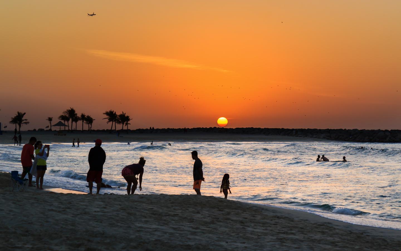 Family is having fun on Al Mamzar Beach at sunset