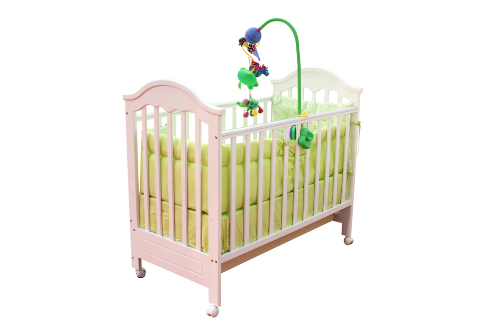 A small pink baby crib on rollers against a white background
