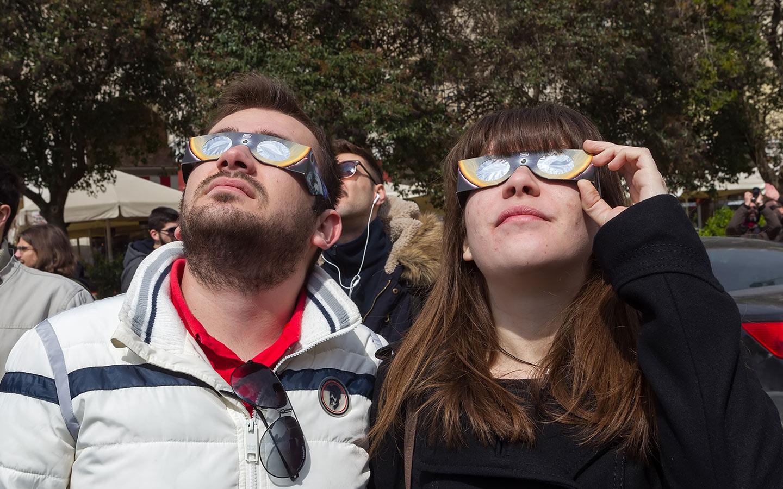 شخصان يرصدان كسوف الشمس باستخدام النظارات المخصصة