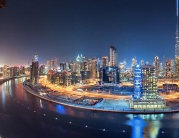 night view of buildings along Dubai Water Canal