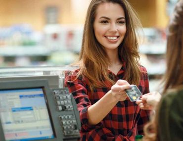 woman is paying for the goods she bought at the supermarket