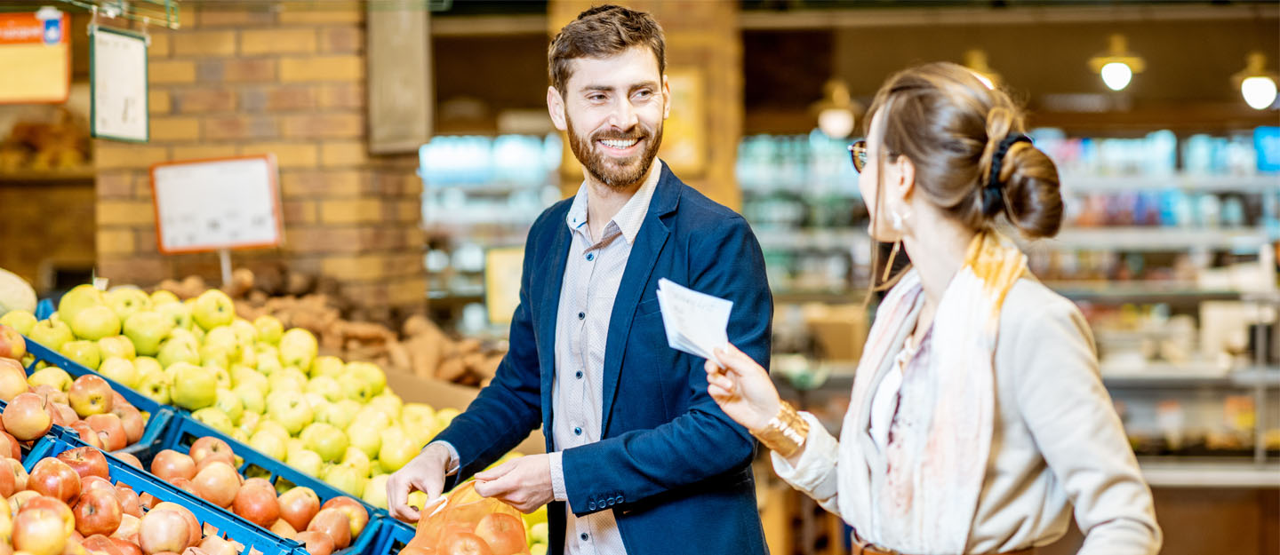A happy couple buying grocery items from a supermarket