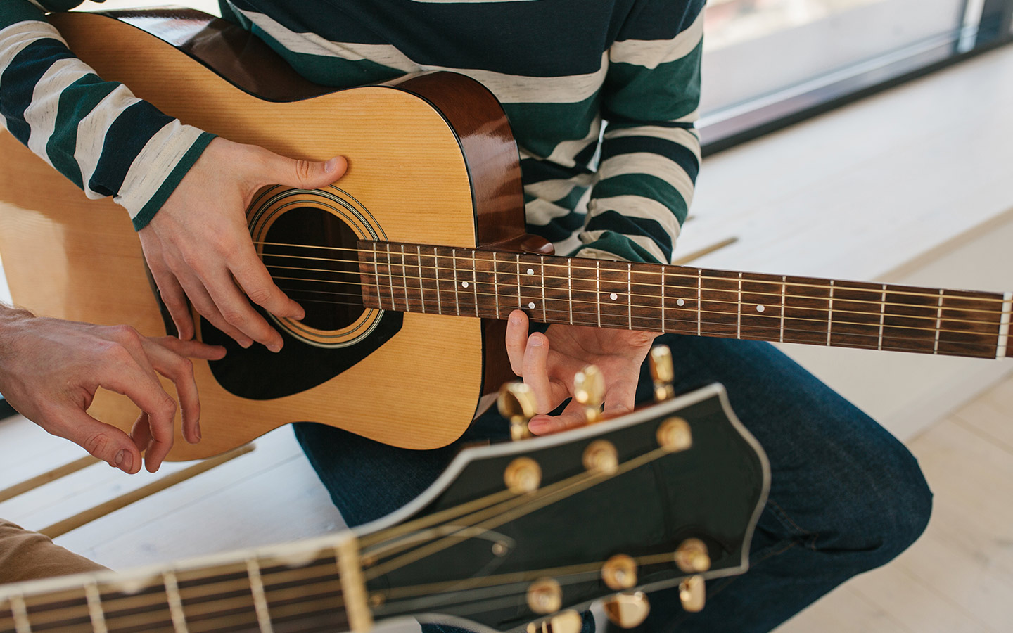 two men practising a song on guitar