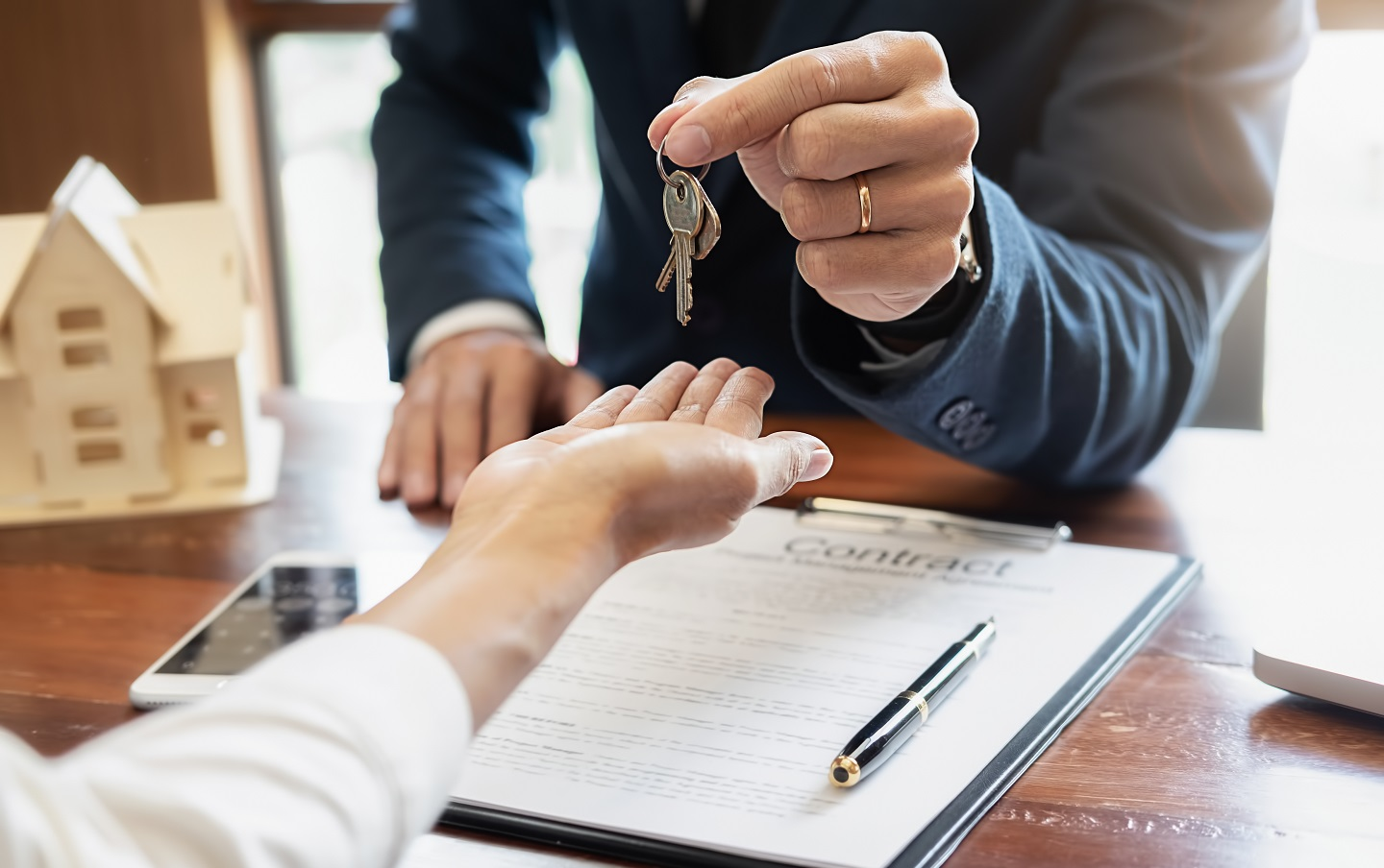 A man is giving keys of a home to a buyer
