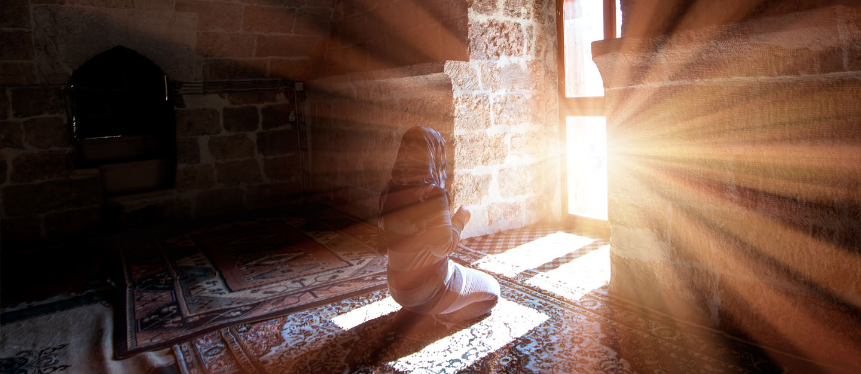 Sunlight shines on a woman praying