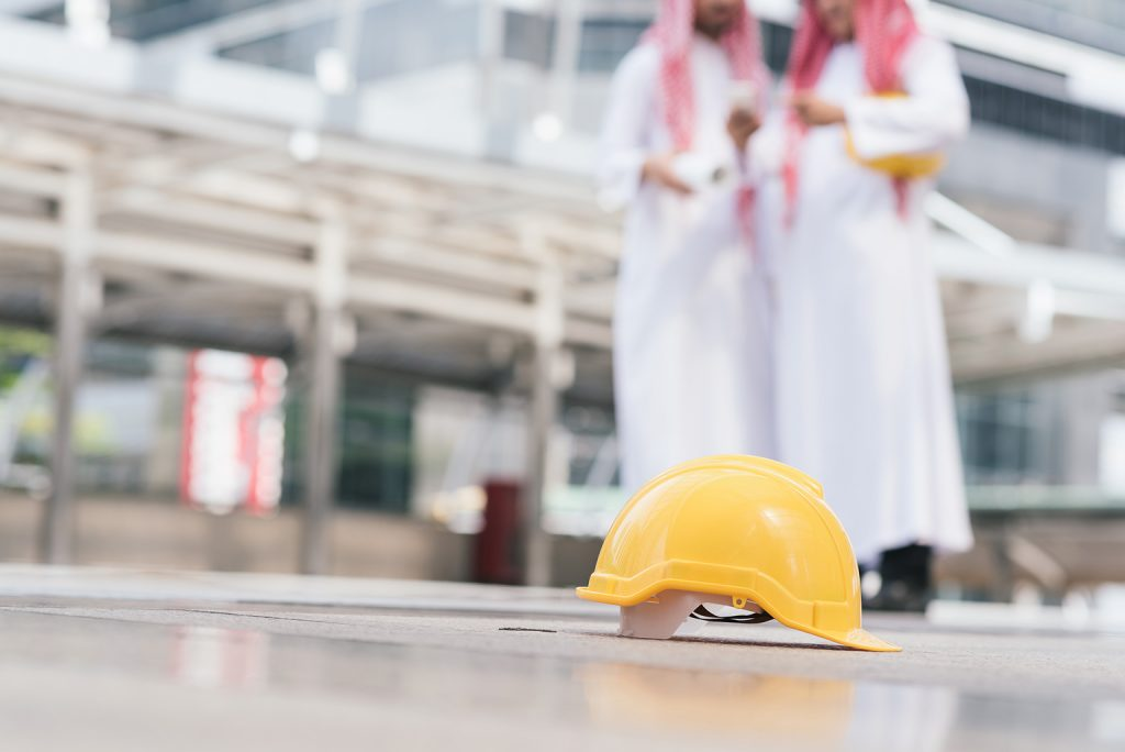 Two Emirati men in traditional clothing conversing in a factory with a yellow construction workers helmet lying on the ground nearby