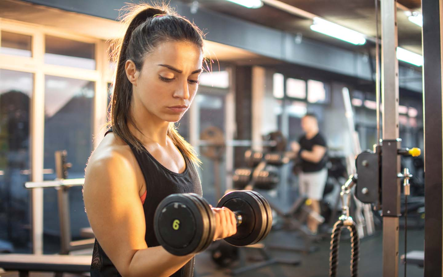 Young woman lifting weights at a gym